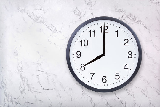 Wall clock show eight o'clock on white marble texture. Office clock show 8pm or 8am on marble background