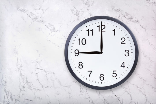 Wall clock show nine o'clock on white marble texture. Office clock show 9pm or 9am on marble background