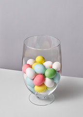 Multi-colored painted eggs in a glass vase on a gray background with space for text. Easter concept