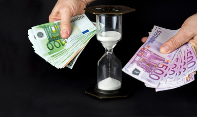 Hourglass and paper money. Time is money concept