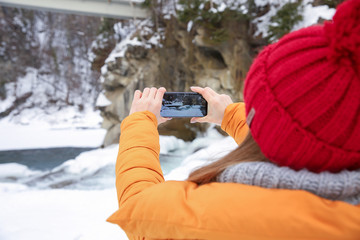 Beautiful woman taking picture of mountain river at snowy resort