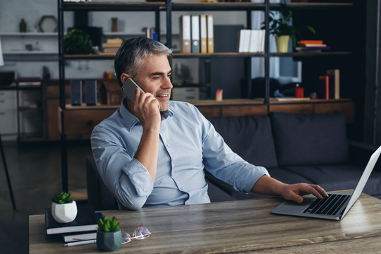 Mature man talking by phone while working on laptop in office