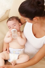 Naked baby with feeding bottle sleeping at mum