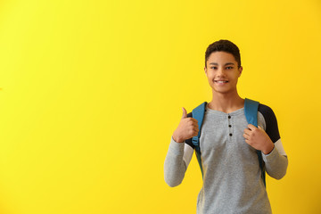 African-American schoolboy showing thumb-up on color background