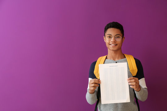 African-American boy with answer sheet for school test on color background