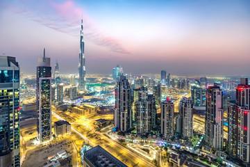 Colourful nighttime skyline of a big modern city. Dubai, United Arab Emirates. Aerial view.