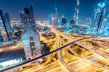 Colourful nighttime skyline of Dubai, United Arab Emirates. Aerial view on highways and skyscrapers.