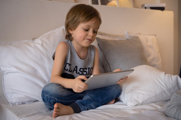 5 year old boy lying In bed playing game on tablet in bedroom,Education school technology internet concept