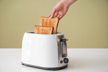 Woman taking bread slice from toaster on table
