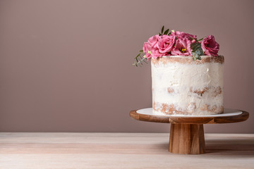 Sweet cake with floral decor on table against color background