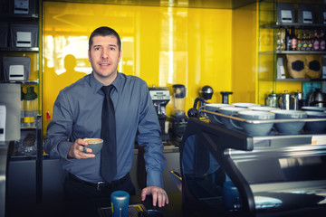 Portrait of small business owner smiling and standing behind counter inside coffee shop – Successful young man working in trendy cafe store holding delicious cup of coffee