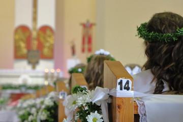 Obraz Udekorowana odświętnie ławka z numerem 14 w kościele, dziewczynki w komunijnych białych strojach i wiankach na głowach, siedzą tyłem, rozmyte, w oddali ołatrz, krzyż - fototapety do salonu