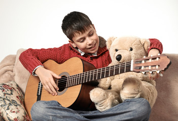 boy plays with an acoustic guitar, sits on the sofa with a bear toy
