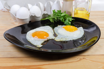 Fried eggs prepared sunny side up on dish and ingredients