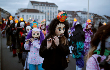 Carnival revellers play their piccolos during the traditional Morgenstreich parade through the streets of Basel
