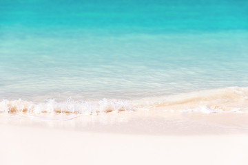 Waves on white sand and turquoise water; summer background
