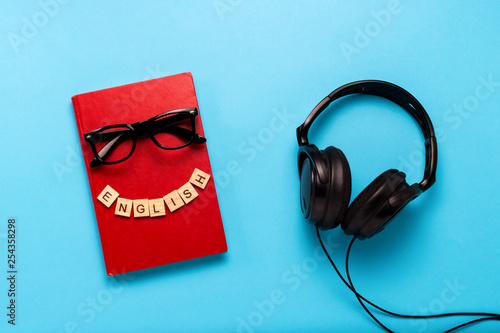 Book with a red cover with text English, glasses and black