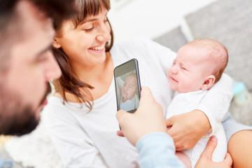 Vater macht Foto von Mutter und Baby