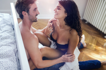 Attractive young sexy woman with her partner in bedroom