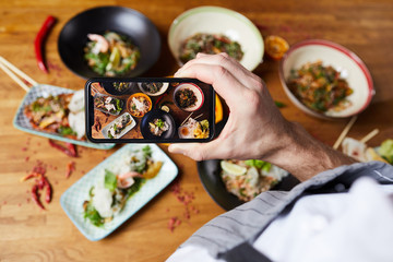 Top view closeup of unrecognizable man taking picture of Asian food dishes, copy space