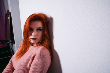 portrait of a red-haired girl at the wall