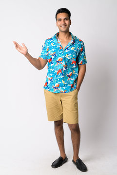 Full body shot of young happy Indian tourist man showing something