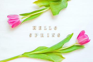 Spring flower background - yellow tulip flowers and wooden inscription Hello Spring on the white wooden background