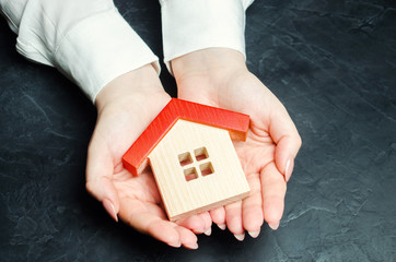 A woman is protecting a miniature wooden house with a red roof. Property insurance concept. Protection of housing. Security and safety family and life. Insurance agent services. Support