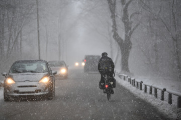 Cyclist drives on a road during heavy snow fall near Munich