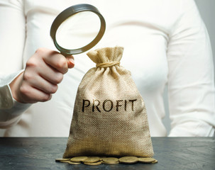 Businesswoman holds a magnifying glass over a money bag with the word Profit. Analysis of the budget in the company. Revenue Analytics. Planning a business. Profitability. Profit maximization