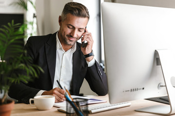 Image of handsome businessman talking on cell phone while working on computer in office