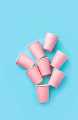 Stack of pink drinking paper cups on mint blue background. Birthday party celebration holiday kids...