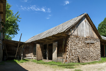 Old rustic wooden barn building in village at summer