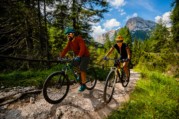 Wall Mural - Cycling woman and man riding on bikes in Dolomites mountains andscape. Couple cycling MTB enduro trail track. Outdoor sport activity.