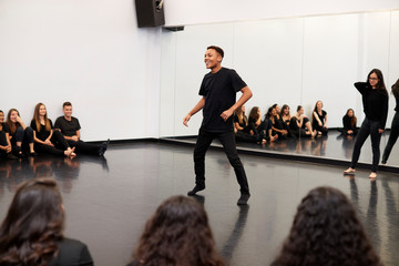 Male Student At Performing Arts School Performs Street Dance For Class And Teacher In Dance Studio