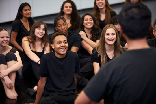 Teacher At Performing Arts School Talking To Students Sitting On Floor In Rehearsal Studio