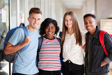 Portrait Of Smiling Male And Female College Student Friends In Corridor Of Building
