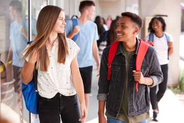 Group Of Smiling Male And Female College Students Walking In School Building Corridor