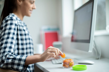 Female Worker In Office Having Healthy Snack Of Dried Apricots At Desk