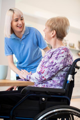 Female Care Assistant Talking To Senior Woman Sitting In Wheelchair At Home