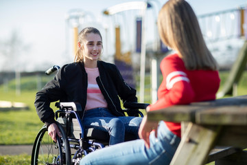 Teenage Girl In Wheelchair Talking With Friend In Park