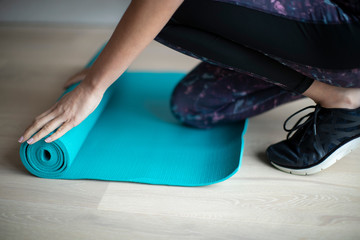 Close Up Of Woman Rolling Out Exercise Mat On Floor Before Exercise