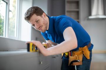 Carpenter Installing Luxury Modern Fitted Kitchen