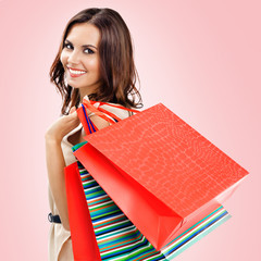 Beautiful woman with shopping bags, over pink