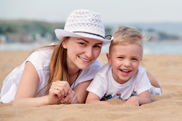906f62905f6 Mom and son smiling lie on sand of beach. Happy little boy son and mother