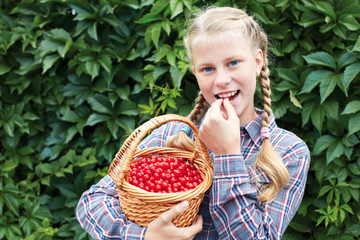 Cheerful girl stands on the background of a green wall in the garden, with a cherry basket in her hands.