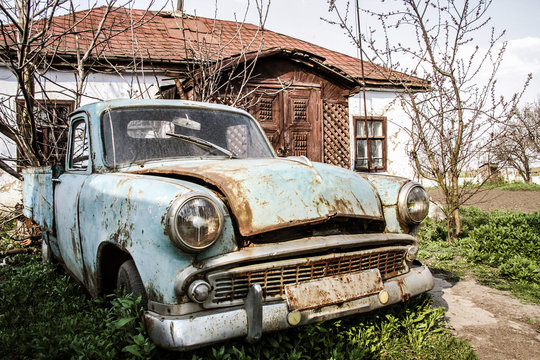 old abandoned retro car in the yard near the house