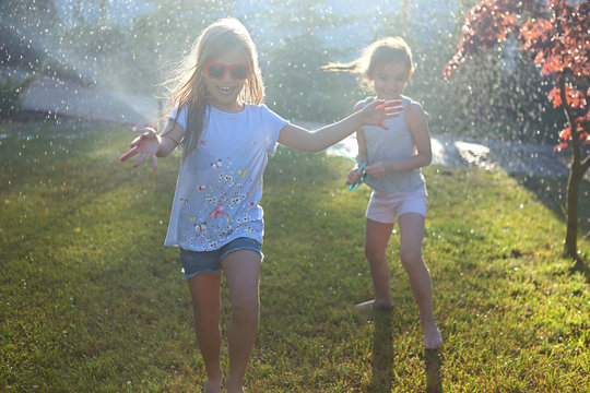 Child playing with garden sprinkler. Kids run and jump. Summer outdoor water fun in the backyard. Child playing with garden sprinkler. Kids run and jump. Summer outdoor water fun in the backyard