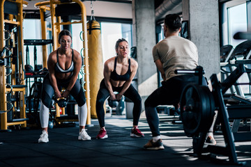 Young muscular people in sportswear working out with kettle bells at the gym.