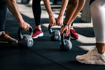 Group people in sportswear holding dumbbells during workout at the gym, low angle, close-up.